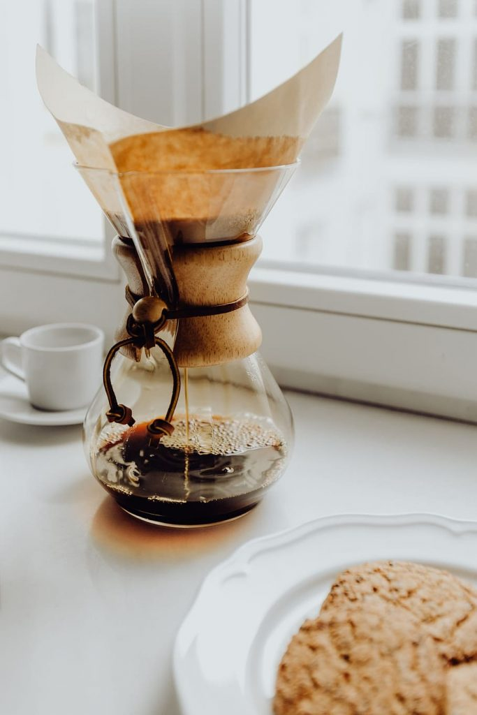Chemex coffee maker on white windowsill with cup of coffee beside it and cookies on a plate in the corner